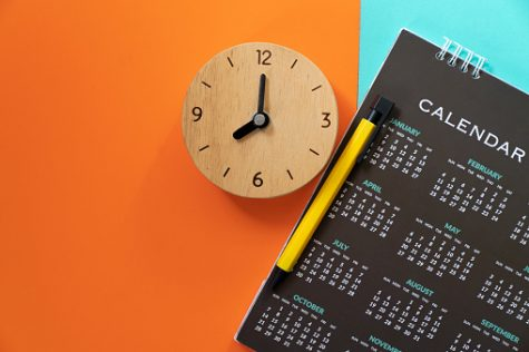 close up of calendar, alarm clock and pen on the color table, planning for business meeting or travel planning concept