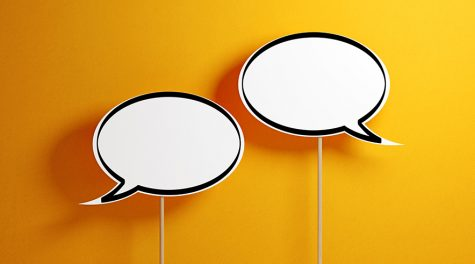 White chat bubbles with wooden sticks on yellow background. Horizontal composition with copy space.